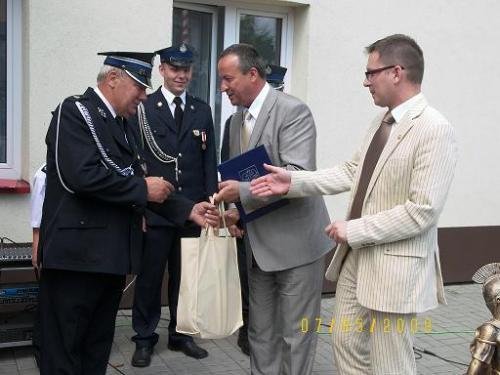 Komendant OSP   w Woli Krzysztoporskiej Zbigniew Galuś przyjmuje gratulacje od Przewodniczącego Rady Powiatu Andrzeja Jarosa.